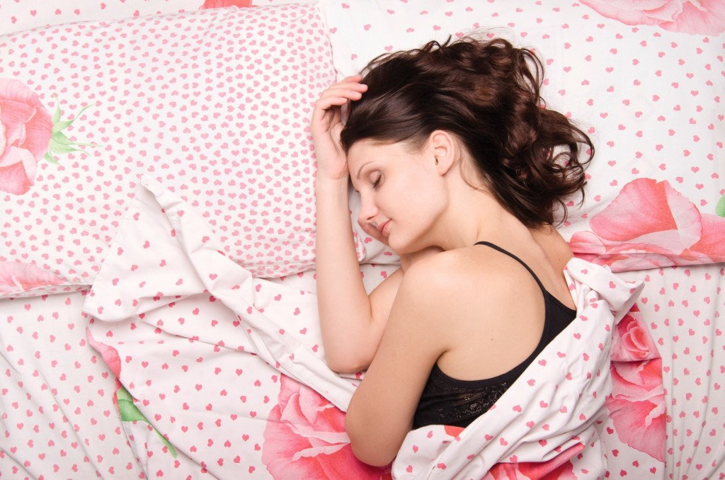 Young beautiful girl sleeping alone in bed